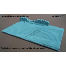 Cobblestones street with stone wall